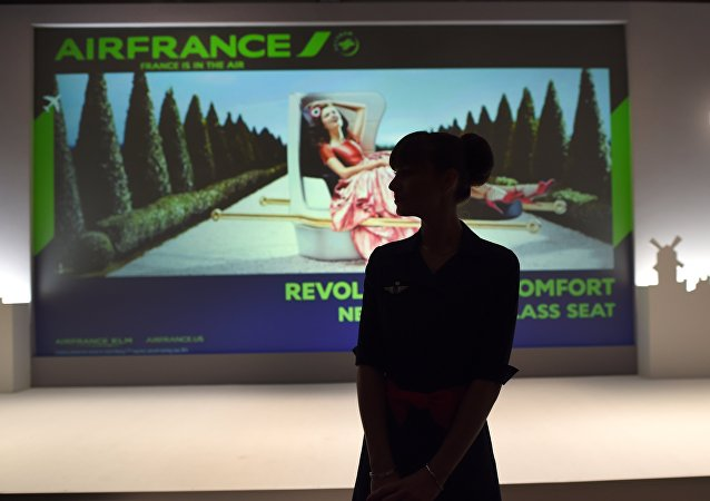 An Air France flight attendant looks at a screen at the new Air France Exhibition called Air France,france is in the Air