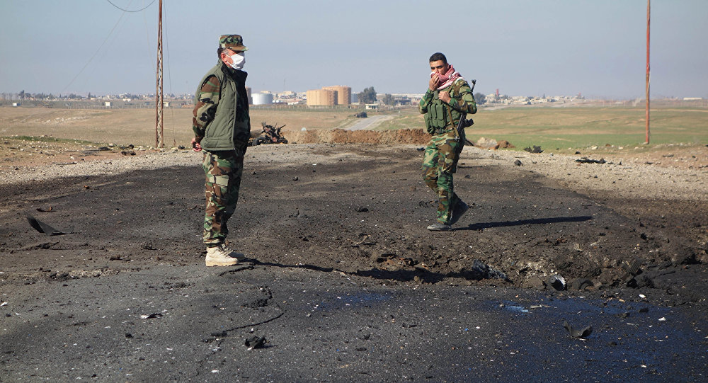 In this undated photo made avaialble Saturday, March 14, 2015, by the Kurdistan Region Security Council (KRSC), Kurdish soldiers survey the site of a bomb attack on a road between Mosul, Iraq, and the Syrian border in northern Iraq