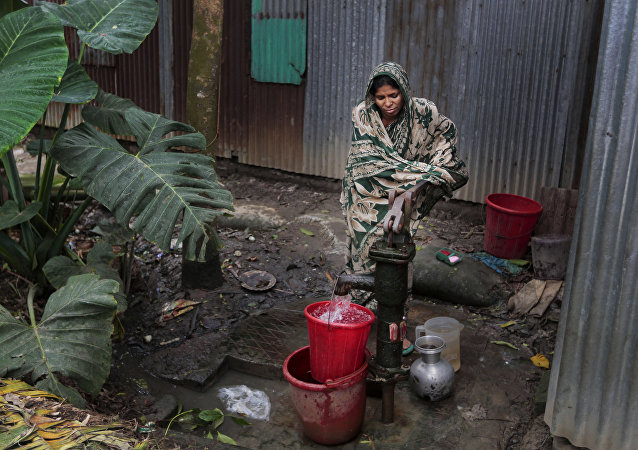 In this April 5, 2016 photo, a Bangladeshi woman collects arsenic-tainted water from a tube-well in Khirdasdi village, outskirts of Dhaka, Bangladesh