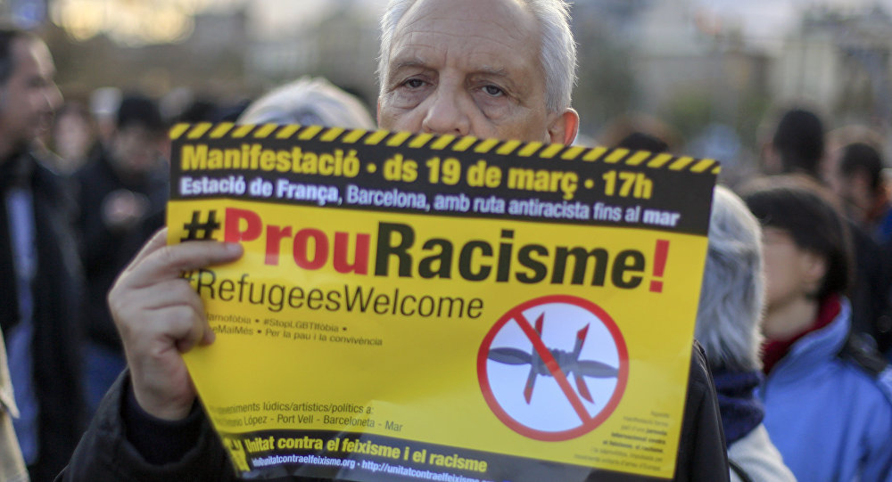 """A protester called by Stop Mare Mortum and """"Unity against Fascism and Racism"""" platforms, holds a poster reading Stop Racism in Catalan during the European March for Refugee Rights in Barcelona on March 19, 2016."""