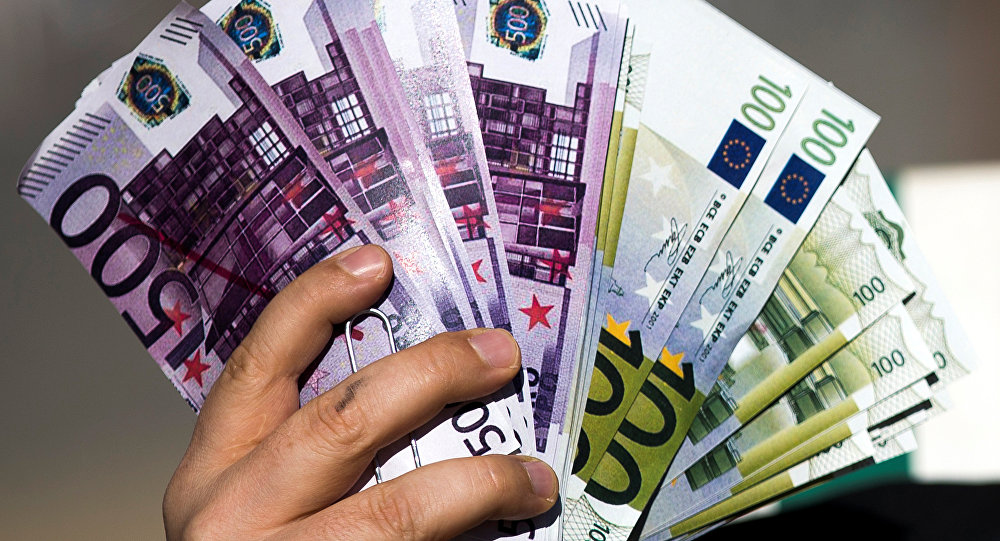 An activist shows fake banknotes during a demonstration outside the European Commission (EC) headquarters.