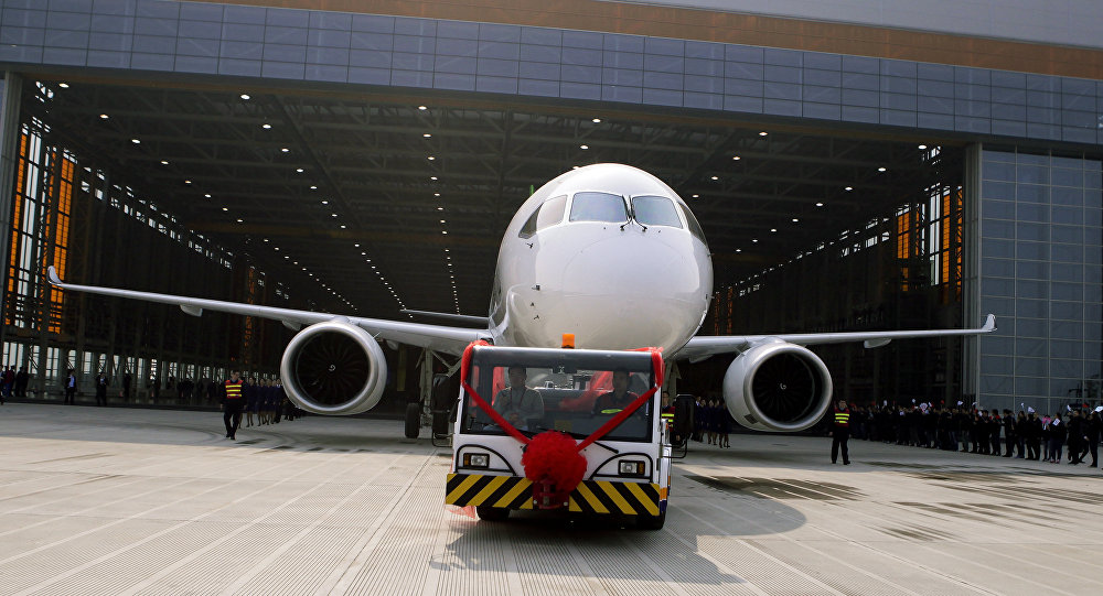 Chinese workers wave flags as a truck pulls out the first twin-engine 158-seater C919 passenger plane made by The Commercial Aircraft Corp. of China (COMAC) during a ceremony at the company's hangar near the Pudong International Airport in Shanghai, China. (File)