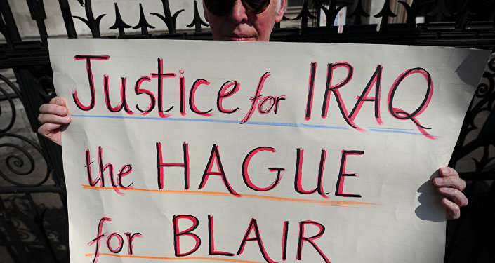 An anti-war protester holds a placard that reads Justice for Iraq, the Hague for Blair during a demonstration outside the High Court in central London on May 28, 2012.