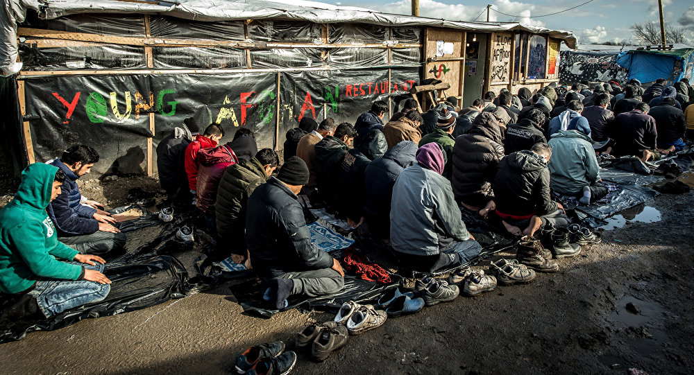 Men pray  in the migrants and refugee camp in Calais, northern France. File photo
