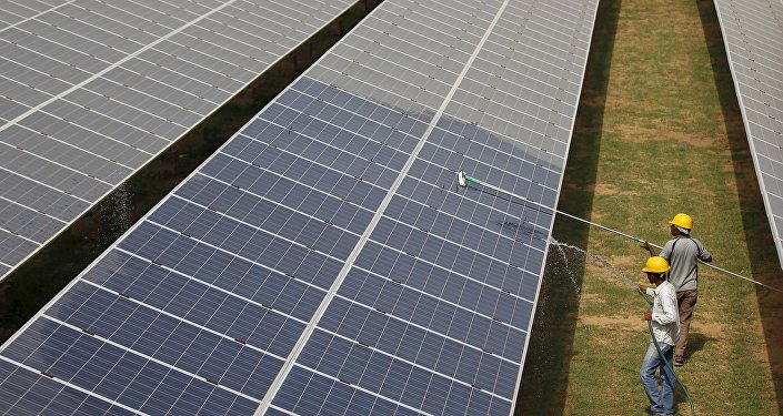 Workers clean photovoltaic panels inside a solar power plant in India (File)