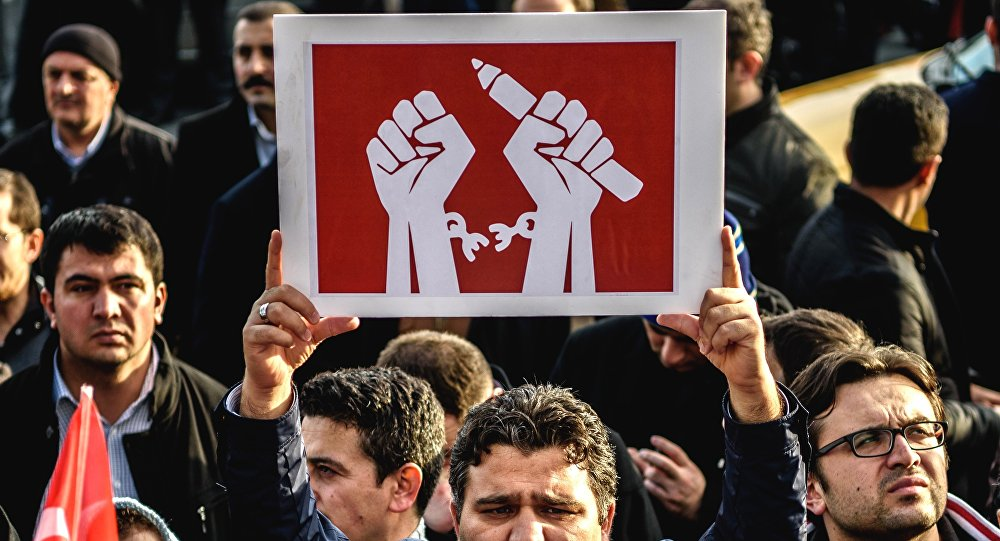 A man holds up a placard as people demonstrate in support of Turkish daily newspaper Zaman in front the headquarters in Istanbul on March 4, 2016.