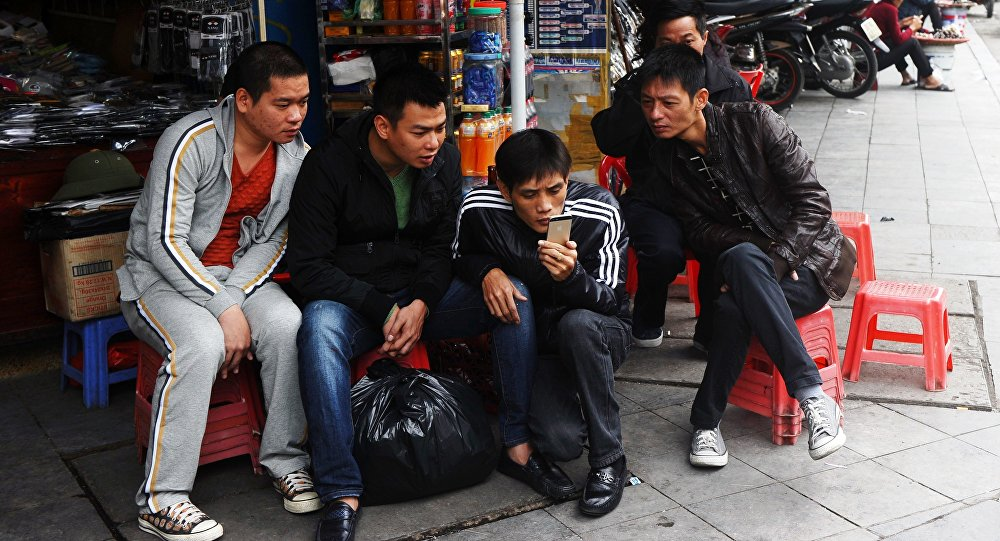 In this picture taken on December 5, 2014, men reads news from a smartphone on a commercial street in downtown Hanoi.