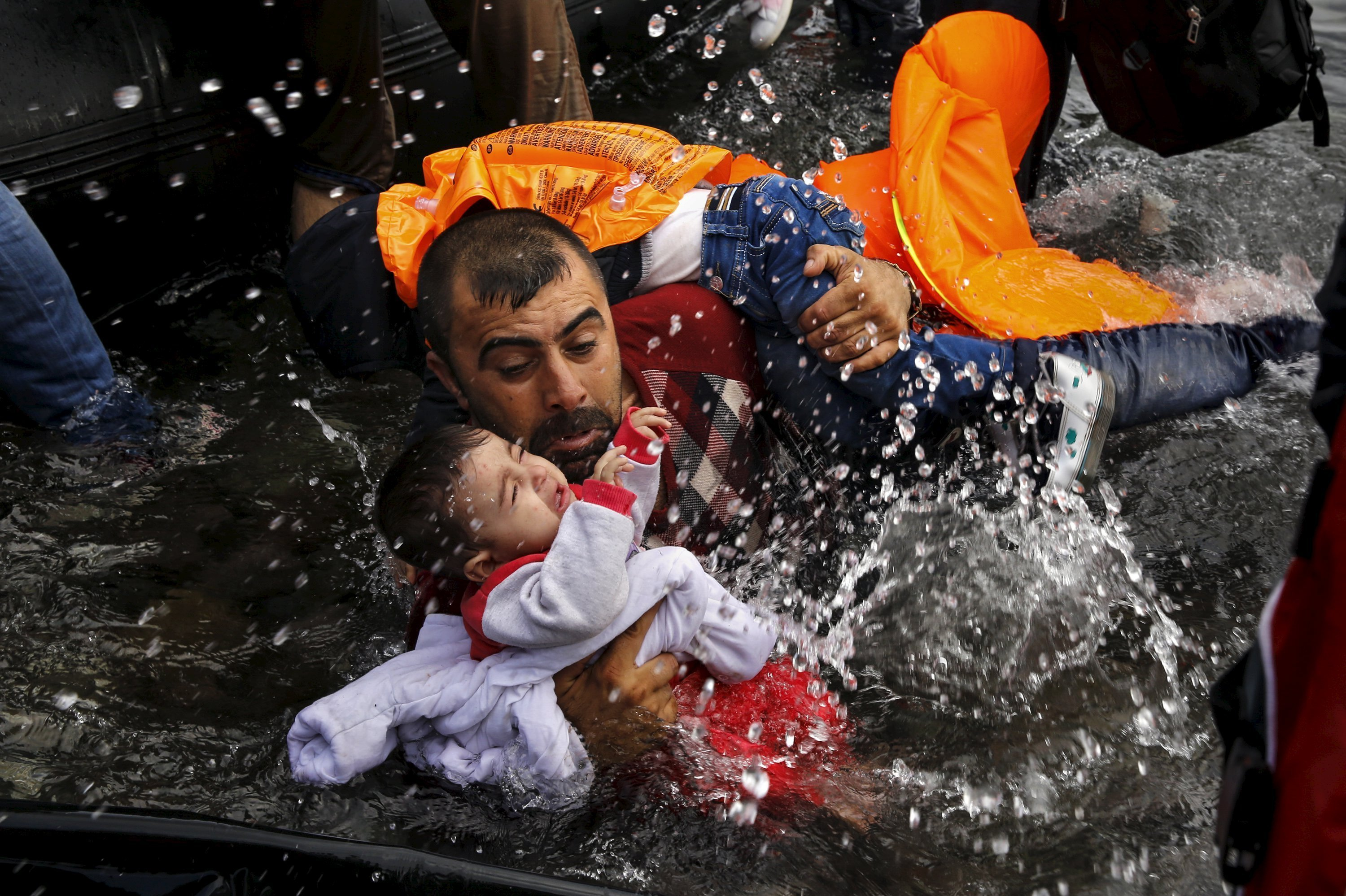 A Syrian refugee holds onto his children as he struggles to walk off a dinghy on the Greek island of Lesbos, after crossing a part of the Aegean Sea from Turkey to Lesbos. file photo