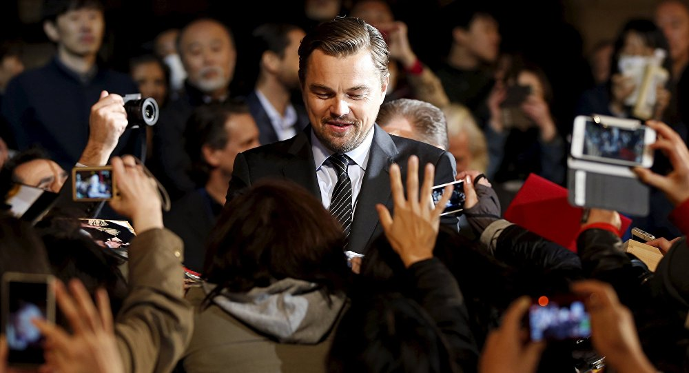 Oscar-winning actor Leonardo DiCaprio (C) signs autographs for fans during the Japan premiere of his movie The Revenant in Tokyo, Japan, March 23, 2016