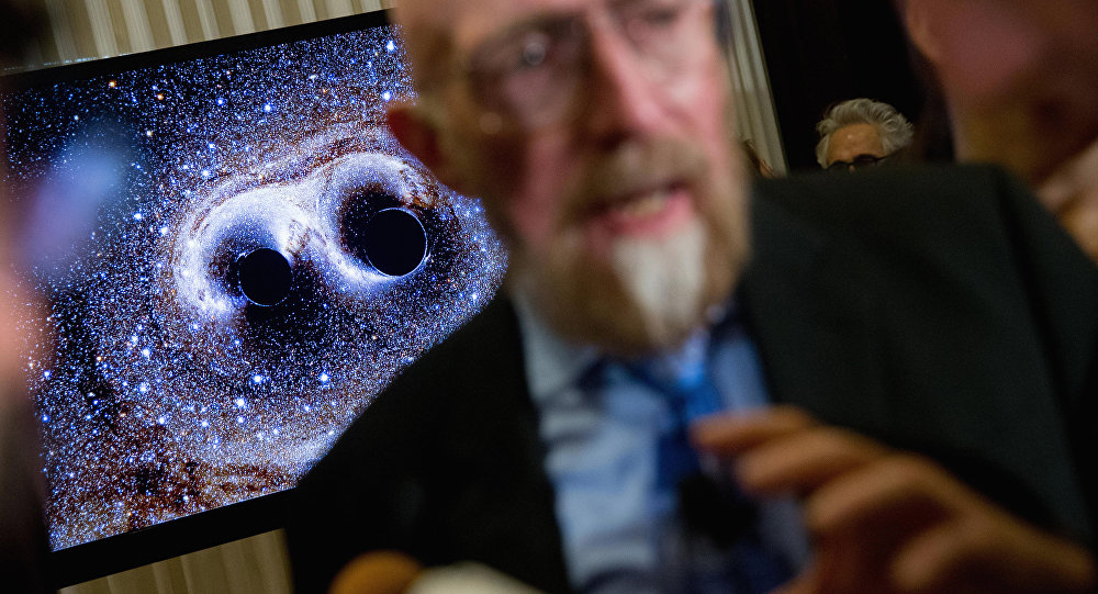 visual of gravitational waves from two converging black holes is depicted on a monitor behind Laser Interferometer Gravitational-Wave Observatory (LIGO) Co-Founder Kip Thorne as he speaks to members of the media following a news conference at the National Press Club in Washington, Thursday, Feb. 11, 2016