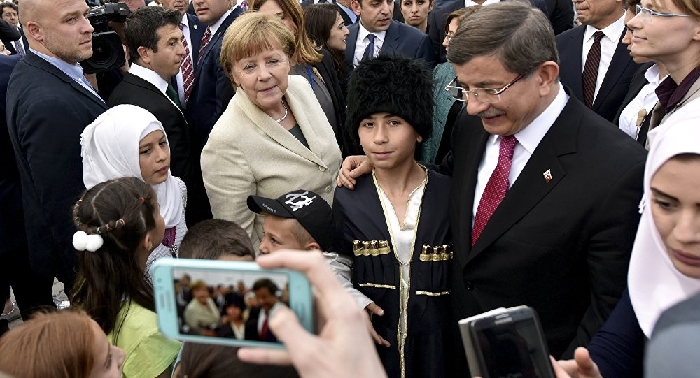 Turkish Prime Minister Ahmet Davutoglu and German Chancellor Angela Merkel pose for a picture with refugees in Nizip refugee camp near Gaziantep, Turkey, April 23, 2016