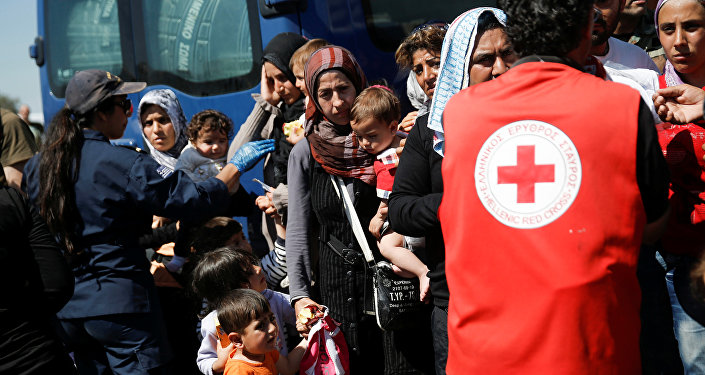 A woman holds two children as refugees and migrants wait to board a bus that will transfer them from a makeshift camp at the port of Piraeus to a newly built relocation centre in the port town of Skaramagkas, in western Athens, Greece April 18, 2016