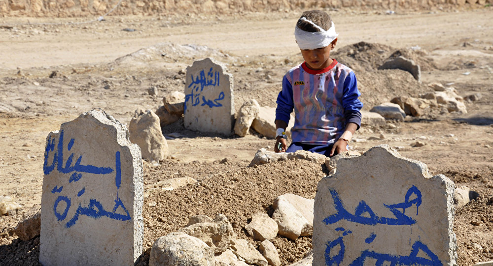 Ali Hamza, 8, sits at the graves of his brother, Mohammed, and sister Asinat, who were killed at their school when a suicide car bomb attack near Qabak elementary school in the Shiite Turkomen village of Qabak, just outside the town of in Tal Afar (File)