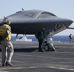 Flight deck crew preparing to launch the X-47B, an experimental unmanned drone aircraft, aboard the USS Theodore Rosevelt, off the coast of Virginia, Sunday, Nov. 10, 2013