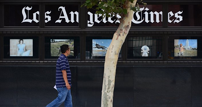 A pedestrian walks past a display of photographs at the Los Angeles Times Building in downtown Los Angeles, California on July 10, 2013