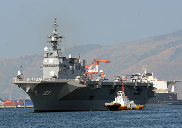 Japanese helicopter carrier Ise is towed as it prepares to dock at the former US naval base, Subic port, north of Manila on April 26, 2016.