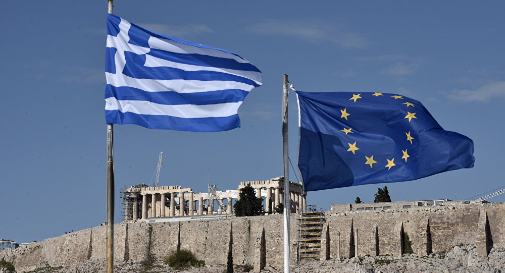 The Greek and EU flags flutter in front of the ancient Acropolis hill in Athens