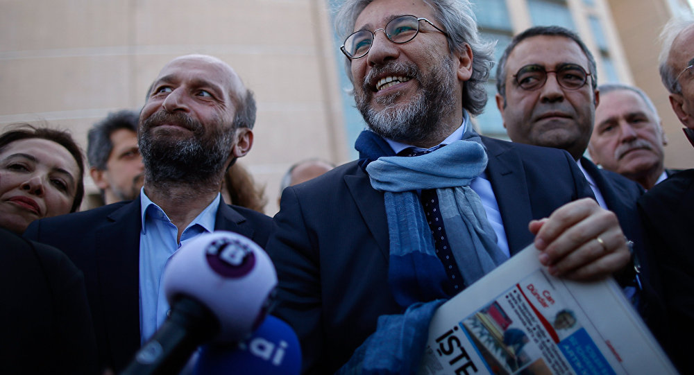 Can Dundar, the editor-in-chief of opposition newspaper Cumhuriyet, right, and Erdem Gul, the paper's Ankara representative, left, speak to the media before the start of their trial in Istanbul