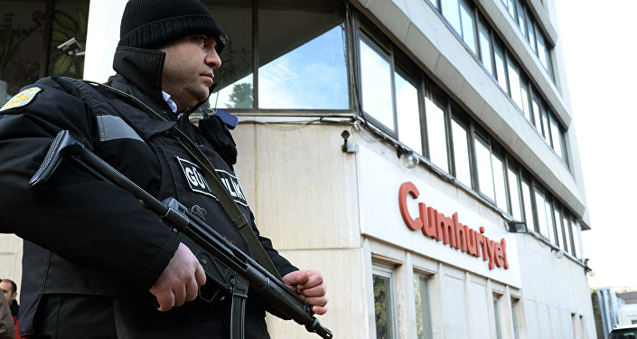 A police officer stands guard at the entrance of Cumhuriyet, the leading pro-secular Turkish newspaper, in Istanbul, Turkey