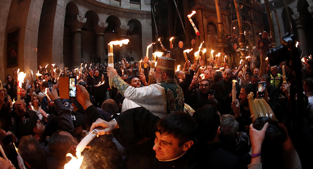 Christian Orthodox worshipers hold up candles lit from the Holy Fire as thousands gather in the Church of the Holy Sepulchre in Jerusalem's Old City (File)
