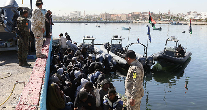 Illegal migrants sit on the dock at the Tripoli port after 115 migrants of African origins were rescued by two coast guard boats at sea when their boat started sinking off the Libyan coast on April 11, 2016