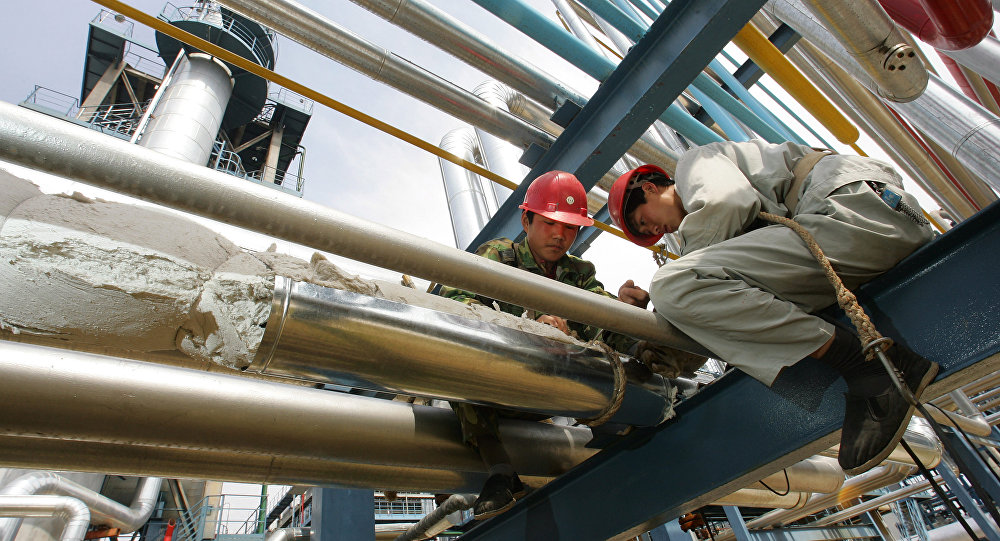 Workers repair pipes at the Yanlian Oil Refinery in Yan'an, 25 May 2005, north of Xian in western China's Shaanxi province