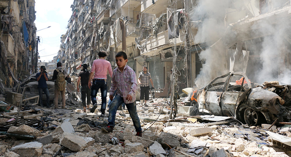 People walk amid the rubble of destroyed buildings following a reported air strike on the rebel-held neighbourhood of al-Kalasa in the northern Syrian city of Aleppo, on April 28, 2016
