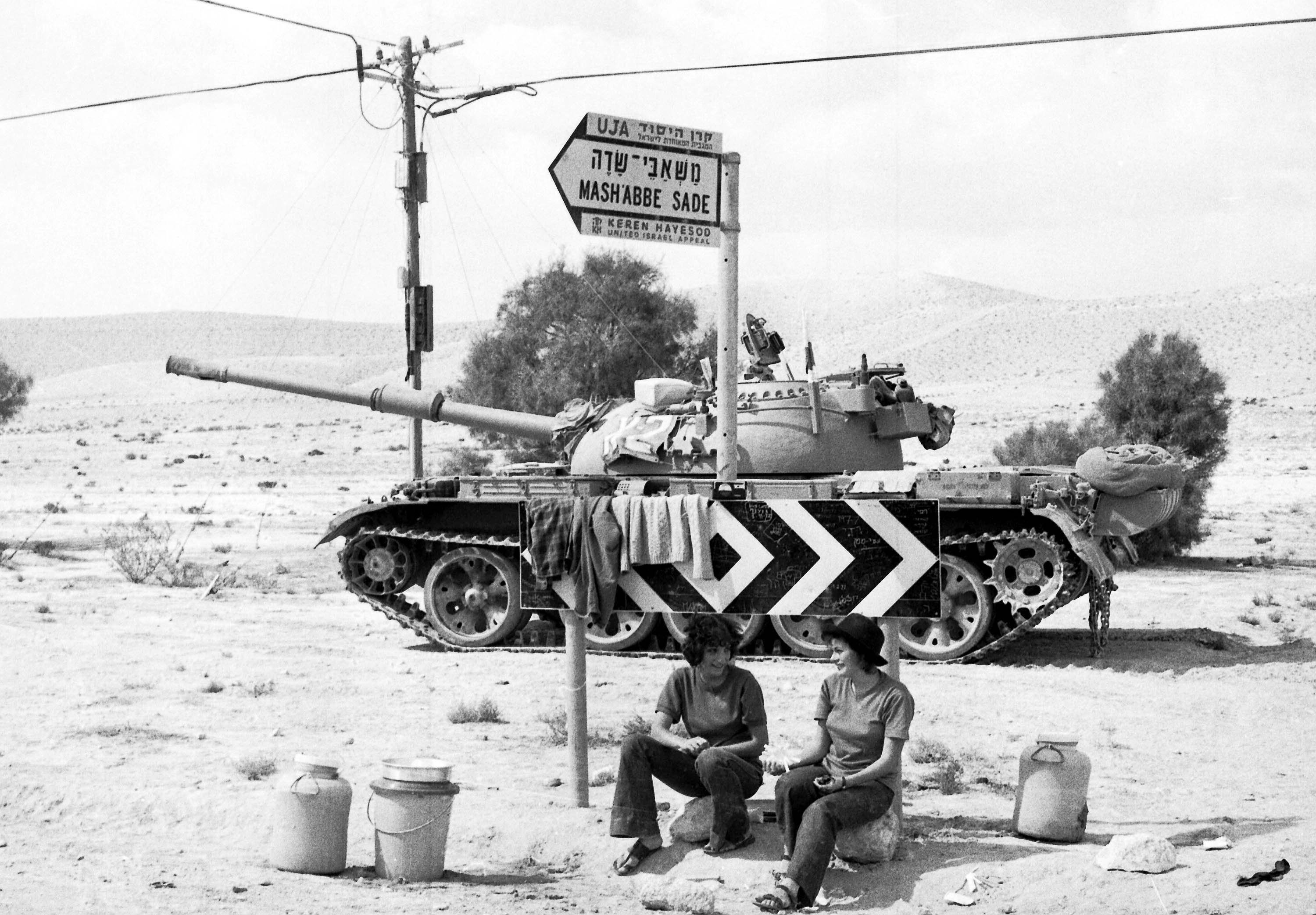Two Israeli Army girls sit beneath a road sign, with a tank in the background, somewhere in the Sinai Desert, Oct. 8, 1973