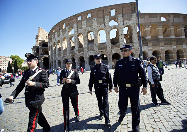 In this Monday, May 2, 2016 photo released by China's Xinhua news agency, Chinese police Shu Jian, third from left, and Sa Yiming, second from left, together with two Italian police officers, check documents of a Chinese tourist group outside the Colosseum in Rome