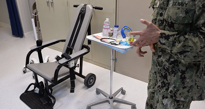 This photo reviewed by the US military and made during an escorted visit shows a US naval medic explaining the feeding chair procedures at the detention facility in Guantanamo Bay, Cuba, April 9, 2014.