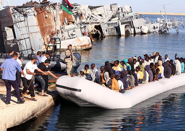 The Libyan coastguard pull a boat carrying illegal African migrants, 'rescued' as they were trying to reach Europe, at a naval base near the capital Tripoli on 29 September 2015.