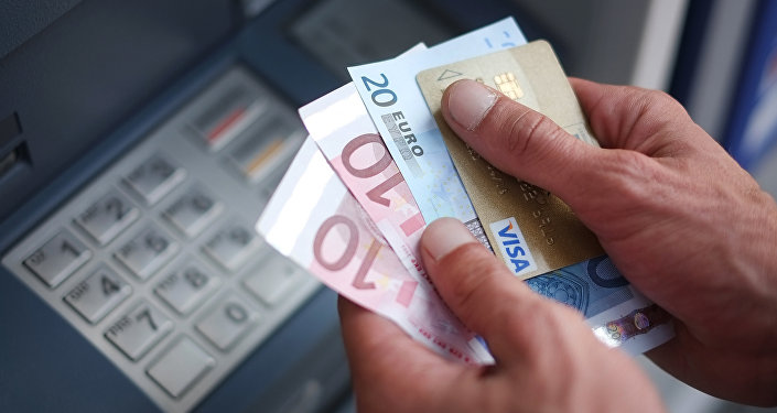 A man takes out Euro banknotes from an automated teller machine (ATM)
