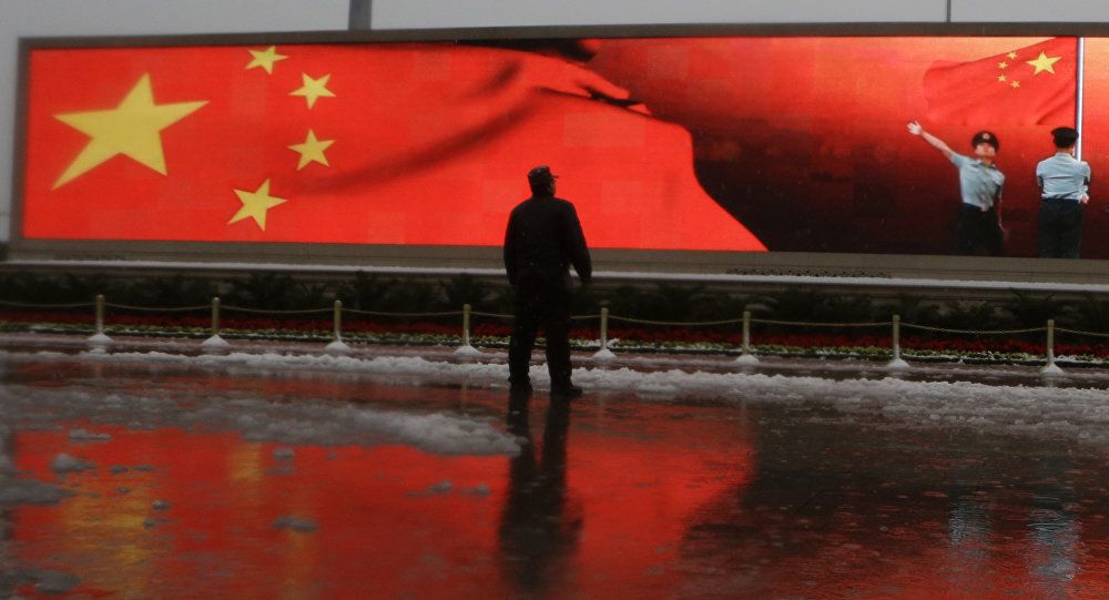 Chinese man stands near a screen displaying the Chinese national flag
