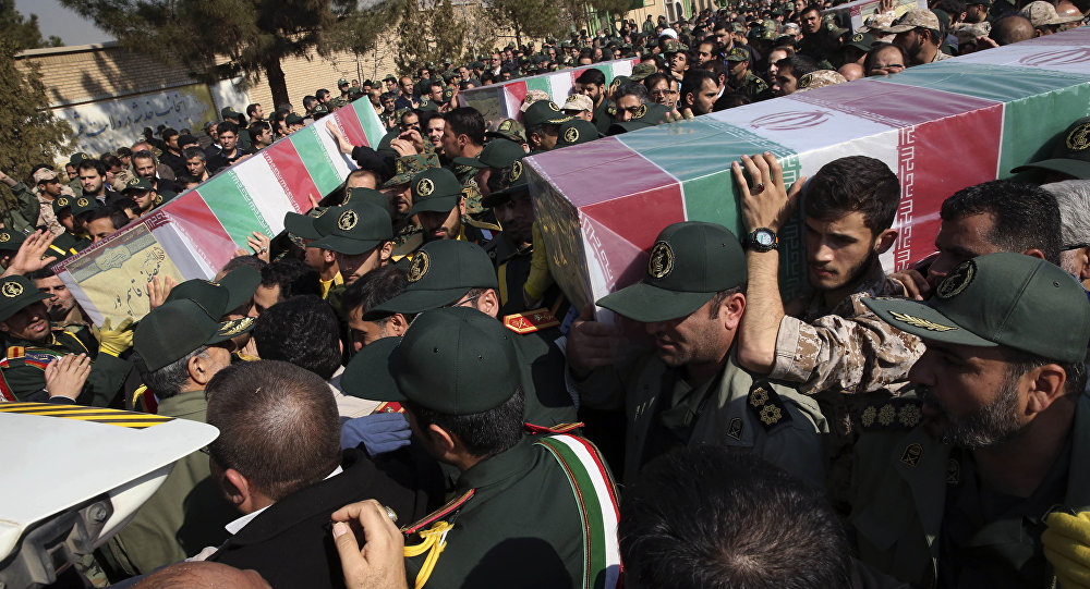 Civilians and armed forces members carry the flag draped coffins of Iranian Revolutionary Guard