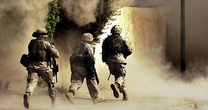 U.S. Marines from the 2nd Battalion, 5th Marine Regiment, run to a building after detonating explosives to open a gate during a mission in Ramadi in Anbar province, Iraq