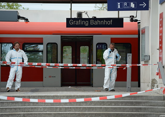 Police officers investigate at the scene of a stabbing at a station in Grafing near Munich, Germany, Tuesday, May 10, 2016