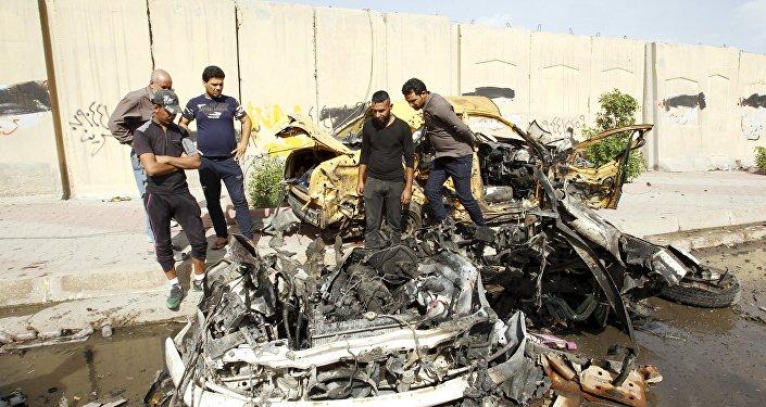 Iraqi men inspect the site of car bomb attack in Baghdad, Iraq (File)