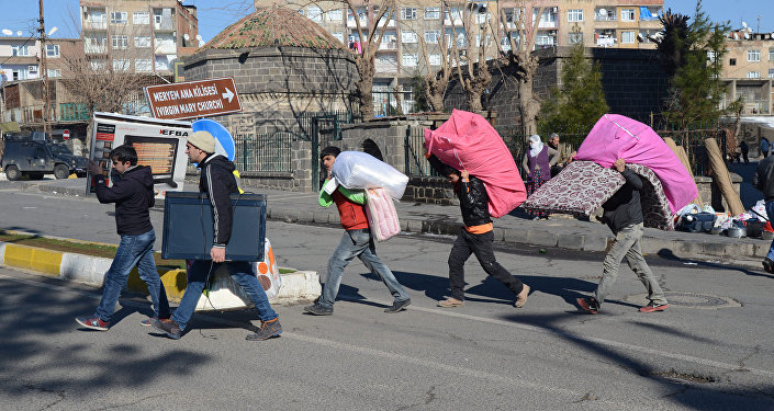 Kurds leave their houses with their belongings after new curfews were imposed in the Sur district of Diyarbakir on January 27, 2016.