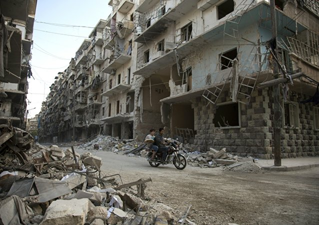 Syrian men ride a motorbike past damaged buildings in the rebel-held Bustan al-Qasr district in eastern Aleppo