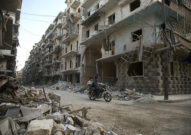 Syrian men ride a motorbike past damaged buildings in the rebel-held Bustan al-Qasr district in eastern Aleppo