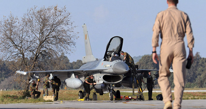 A Belgian pilot walks toward his F-16 fighter jet.