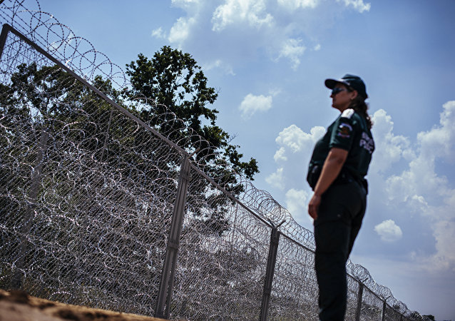 A border police officer stands next to a barbed wire wall on the Bulgarian border with Turkey, near the village of Golyam Dervent