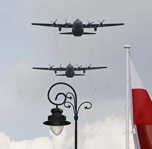 Polish Air Force C-130 Hercules aircraft fly over Poland's national flag during a military parade.