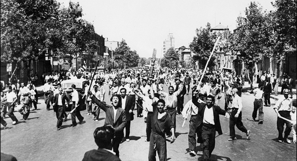 Rioters armed with staves shout slogans, during riots in Tehran, August 1953.
