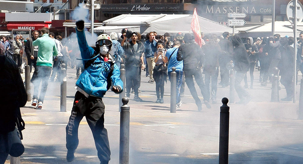 A masked demonstrator throws a tear gas canister during a clash with police, after a demonstration in Marseille, southern France, Thursday, May 12, 2016