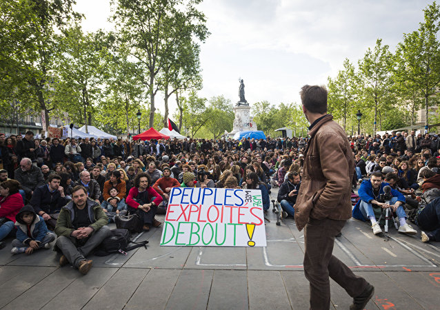 Protester Jean-Baptiste Redde aka Voltuan holds a placard reading 'Exploited people stand up!' as people gather for the general assembly of the Nuit Debout (Up All Night) movement against the French government's proposed labour reforms at the Place de la Republique in Paris on May 15, 2016