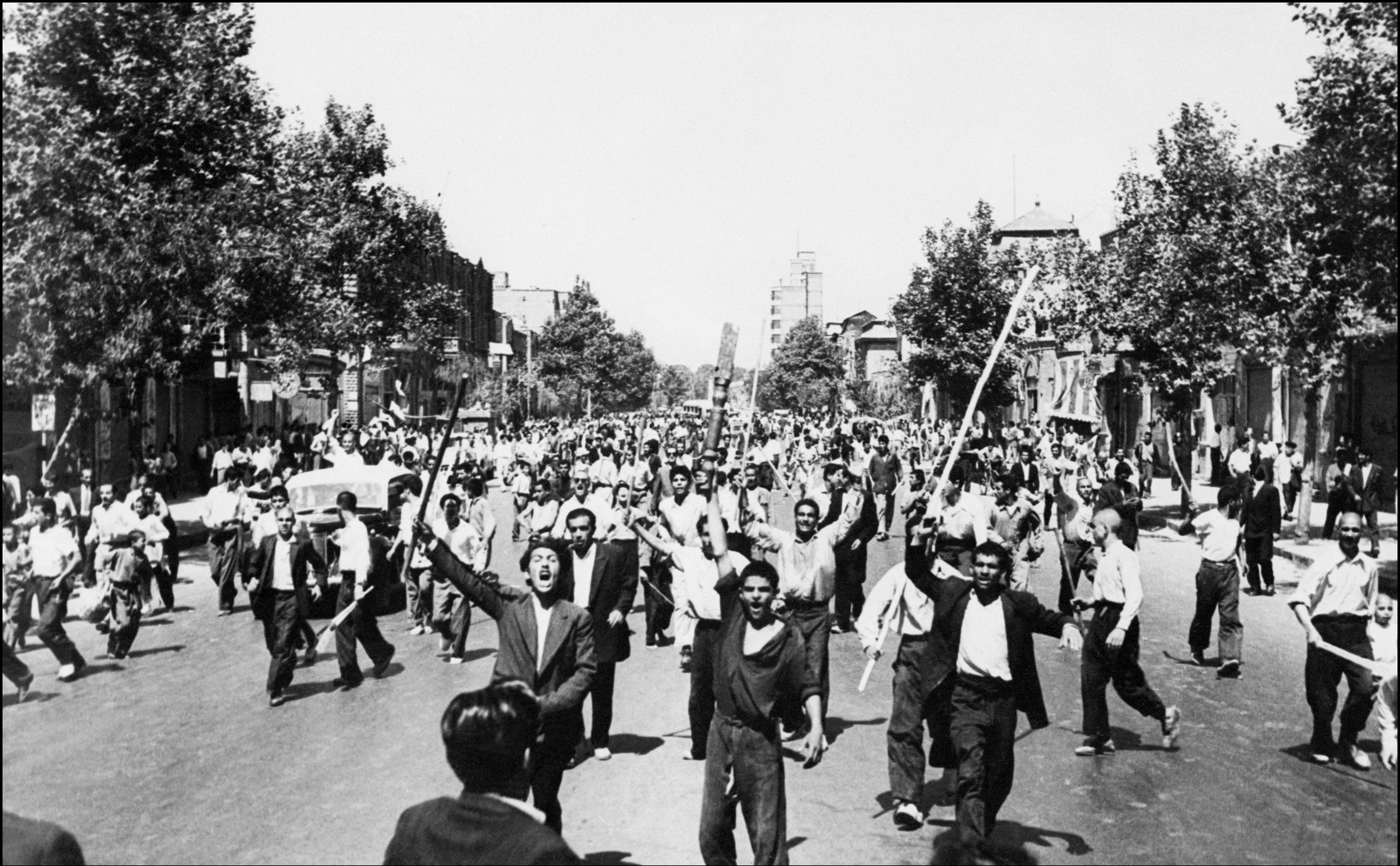 Rioters armed with staves shout slogans, during riots in Tehran, August 1953