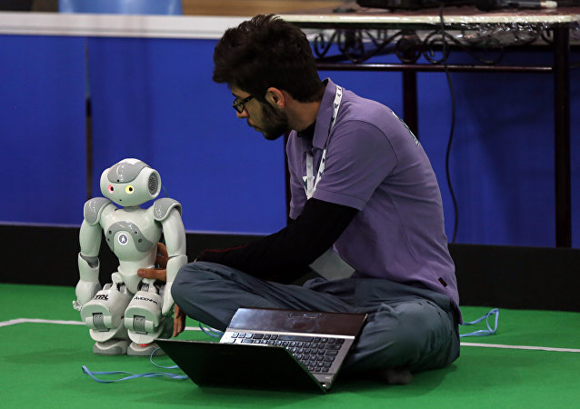 An Iranian sudent from Iran's Azad University of Qazvin checks a robot during the RoboCup Iran Open 2015, in Tehran, on April 8, 2015
