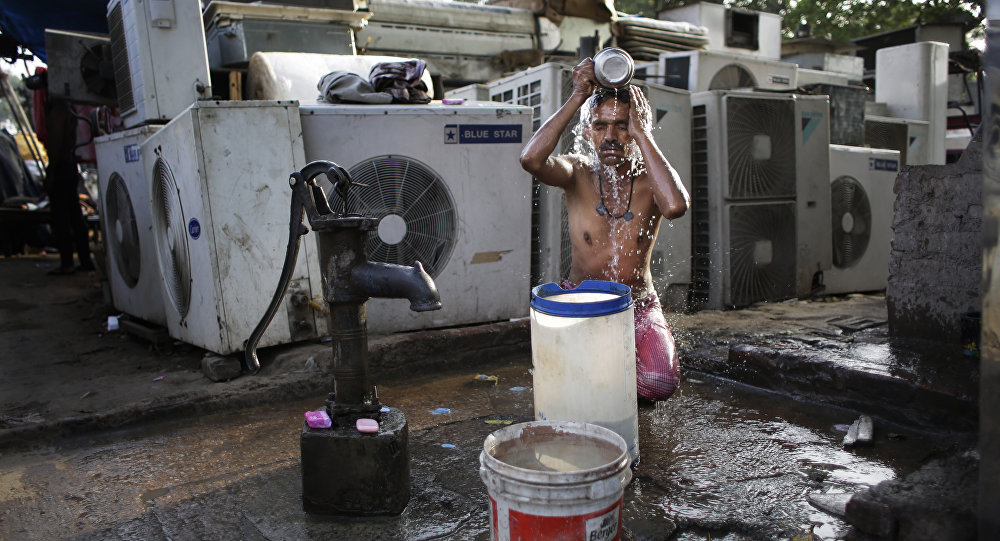 An Indian migrant daily wage worker baths at a public well pump on a hot morning in New Delhi, India, Tuesday, May 17, 2016