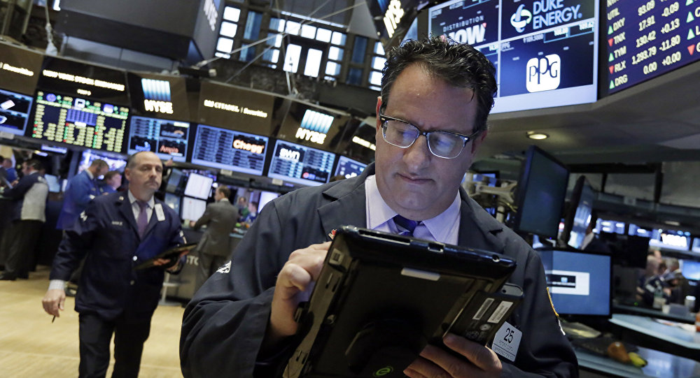 Trader Peter Costa, right, works on the floor of the New York Stock Exchange, Wednesday, May 4, 2016